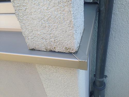 Algenbewuchs aufgrund aufsteigender Feuchtigkeit. Hier fehlt eine Abdichtung zwischen Blech und Putz.