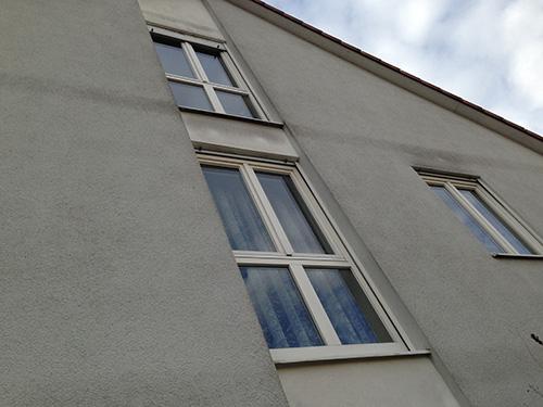 Algenbewuchs an der Fassade aufgrund von Kältebrücken (Deckenstärken zeichnen sich ab).
